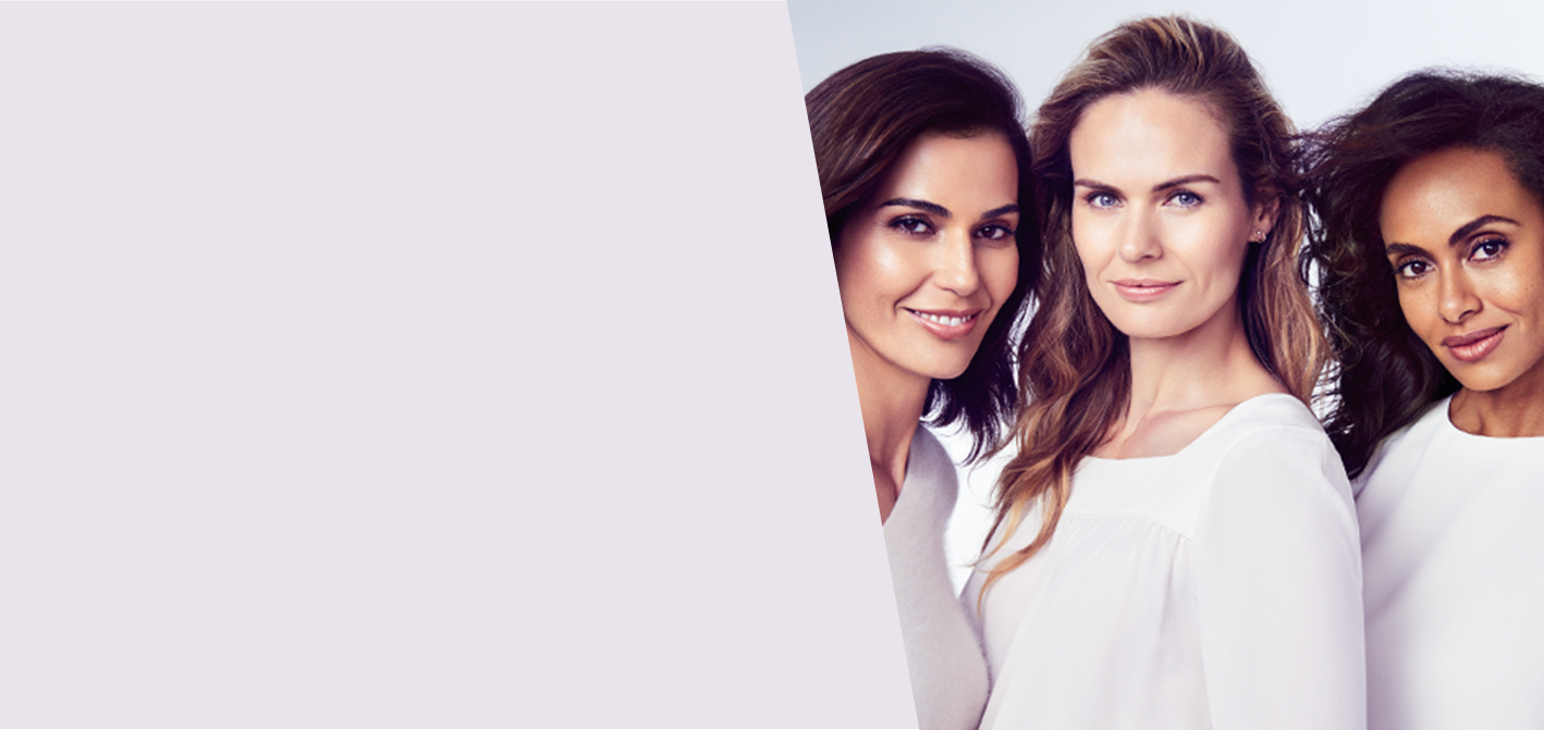 Three women of various ethnicities pose side-by-side and show off youthful skin to promote the Mary Kay TimeWise Repair Volu-Firm set.