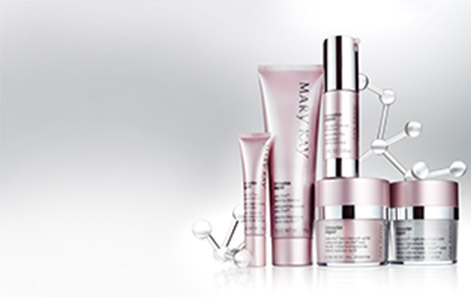 The TimeWise Repair Volu-Firm skin care set from Mary Kay is shown in front of a gray background with silver molecule-like structures behind it.
