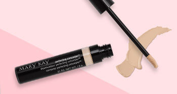 An open tube of Mary Kay Perfecting Concealer is photographed alongside its doe foot applicator and a product smear in front of a two-toned pink background.