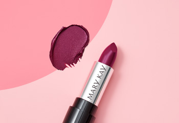 A berry colored Mary Kay lipstick is photographed with its cap off atop a two-toned pink background and alongside a product smear.