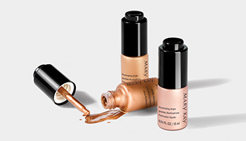 Three bottles of Mary Kay Illuminating Drops are shown with one tipped over and product spilling out.