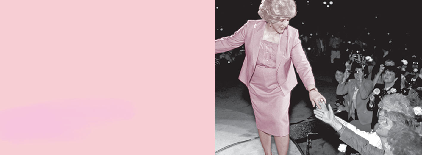 Mary Kay Ash stands on stage and reaches out to members of the Mary Kay independent sales force in an audience.