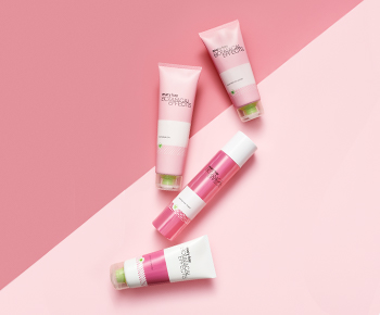 The Botanical Effects skin care set in white and pink tubes on a pink background
