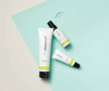 The Clear Proof Acne System in white and green tubes on a teal and gray background