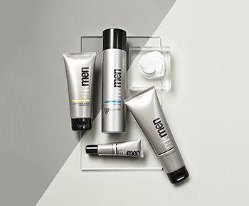 The MKMen Skin Care set in gray tubes on a gray background with a dollop of shave foam