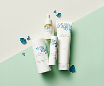 The Mary Kay Naturally products in white packaging with teal leaf illustrations on a green background