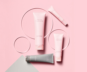 The TimeWise Miracle Set 3D skin care regimen in pink and gray tubes on a pink and gray background